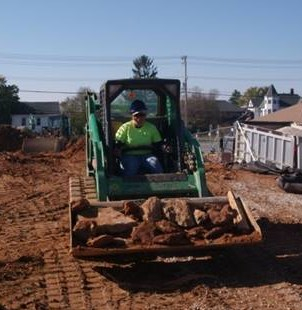 Megan in a fashionable safety yellow shirt and purple hardhat driving a skid-steer loader full of concrete and soil.